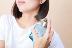 Girl with perfume, young beautiful woman holding bottle of perfu Stock Photography