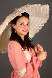 Girl In Period Dress. Teenage brunette girl in period dress and holding a parasol Royalty Free Stock Image