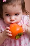 Girl with persimmon Royalty Free Stock Photography