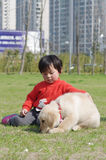 Girl and pet. Chinese girl play withe golden retriever puppy Stock Photo