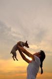 Girl and pet dog at sunset. Asian girl holding up jack russell at sunset Royalty Free Stock Images
