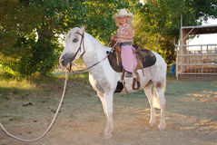 Girl with pet pony. Cute young girl dressed in cowgirl clothes sitting on her pet pony Royalty Free Stock Photography