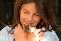 Girl with pet rat. A little girl affectionately cuddling her pet rat royalty free stock photos