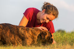 Girl pets her boxer dog. Young girl pets her boxer dog outdoors Royalty Free Stock Images