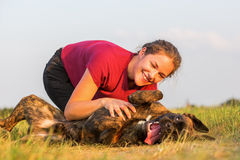 Girl pets her boxer dog. Young girl pets her boxer dog outdoors Stock Images
