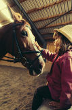 Girl petting horse. Cute girl petting horse before riding lesson Stock Photos