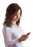 Girl and a phone. Cute brunette girl writing an sms by the cellphone. Isolation Royalty Free Stock Image