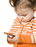 Girl with phone. Little girl is trying to undesrtand how to use mobile telephone Stock Images