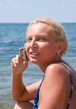 The girl with the phone. The girl speaks by phone on the background of the sea Royalty Free Stock Photo