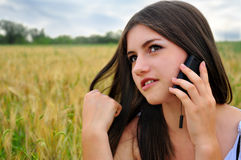 Girl in field talking on the mobile phone. Girl with mobile phone in the wheat field Royalty Free Stock Photography