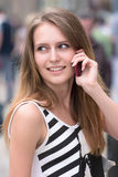 Girl with phone. Portrait of cute girl is talking via mobile phone on the street and smiling Stock Photo