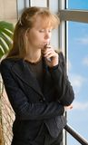 The girl and phone. The girl with phone costs near a window in office building royalty free stock images