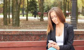 Girl with the phone. The girl with the phone on a bench in the park Royalty Free Stock Photos