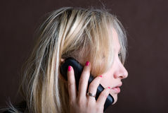 The girl with phone. The young girl talks by black radio to phone Royalty Free Stock Images