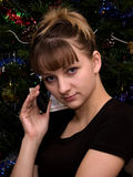 The girl and phone. The beautiful girl speaks by phone near a New Year tree Royalty Free Stock Images