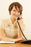 Girl with a phone on a beige Royalty Free Stock Photography