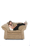 Girl on phone in big chair Royalty Free Stock Photography