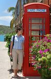 The Girl by The Phone Booth. The girl is standing by the British style phone booth in Nelson's Bay port, the only one XIX century Georgian port in the World that Royalty Free Stock Image
