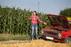 Girl on the phone beside broken car Stock Image