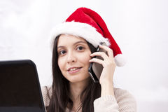 Girl with phone. And computer in Christmas Royalty Free Stock Image