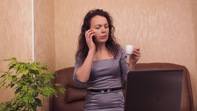 Girl with a phone and a cup of coffee. A woman in a gray dress indoors behind a laptop with a phone is drinking coffee. stock video footage