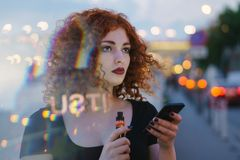 Girl with phone and electronic cigarette. Young attractive girl with red curly hair is holding cell phone and an electronic cigarette. Portrait on background of royalty free stock photos
