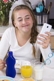 Girl with phone having breakfast in kitchen Stock Photography