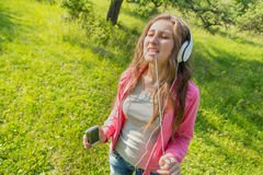 Girl with phone and headphones Stock Photography