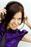 Girl with phone heads. Young woman with phone heads and microphone Stock Photo