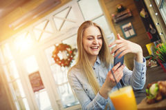 Girl with a phone in her hands resting in a trendy cafe with Christmas decorations Royalty Free Stock Photography