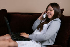 Girl on phone and laptop. Pretty brunette hispanic teenage girl with braces wearing pajamas sitting on sofa or couch typing on laptop and talking on phone royalty free stock photo