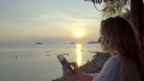 The girl with the phone near the sea on the background of sunset. stock footage