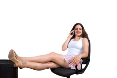 Girl on phone in office chair. A beautiful girl, sitting on a office chair, talking over the phone, smiling Stock Photography