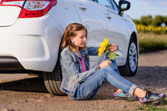 Girl with Phone Sitting on Ground Beside the Car Royalty Free Stock Image