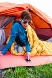 Girl with a phone in a sleeping bag. Stock Photo