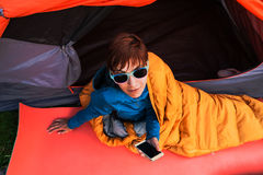 Girl with a phone in a sleeping bag. Royalty Free Stock Photos