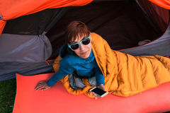 Girl with a phone in a sleeping bag. Royalty Free Stock Photography