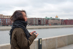 Girl with the phone smiling. On the bank of Moscow-river stock photo
