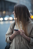 The girl with the phone standing on the street. Somewhere looking into the distance Stock Photo