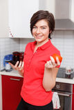 Girl with phone and tomato Stock Image