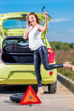 Girl with phone and wrench. Is waiting roadside assistance Royalty Free Stock Photos