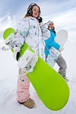 Girl in phones with green snowboard and her friend Royalty Free Stock Photography