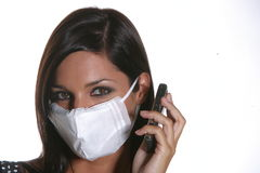 Girl phoning with mask against swine flu. Royalty Free Stock Image