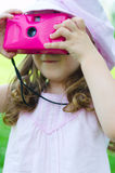 Girl with photo camera. Little girl taking a shot with pink photo camera Royalty Free Stock Photography