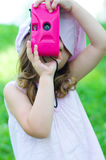 Girl with photo camera. Little girl taking a shot with pink photo camera Royalty Free Stock Photo