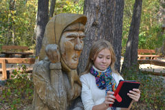 Girl photographed themselves on the plate. Girl photographed themselves on the tablet and a wooden statue royalty free stock image