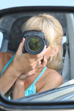 Girl-photographer. The girl-photographer is reflected in a car mirror Stock Images