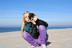 The girl the photographer. Young beautiful female photographer with digital photo camera shutting seaside scene Royalty Free Stock Photo
