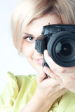 Girl-photographer. Young and beautiful girl with a professional camera in hand Royalty Free Stock Image
