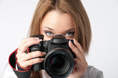 Girl-photographer. Young and beautiful girl with a professional camera in hand Royalty Free Stock Photography